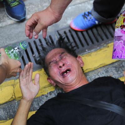 Demonstranter hällde vatten i ansiktet på en man som plågades av tårgasen under söndagens demonstration.