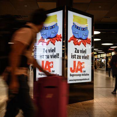 "En person går förbi en valreklamskylt där det står ""Zu viel ist zu viel, ja zur begrenzungs-initiative"""