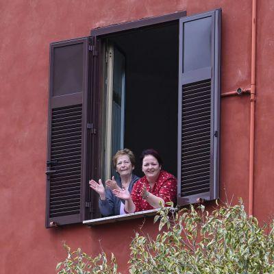 """Två kvinnor vinkar och klappar i händerna. Här under devisen """"En applåd för Italien""""  ( """"Un applauso per l'Italia"""") i distriktet Garbatella i Rom 14.3.2020."""