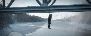 Hirtetty nukke roikkuu sillalta kauniissa lumimaisemassa.