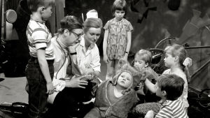 Lääkäri ja hoitaja tutkivat karhupukuun pukeutunutta lasta. Viisi muuta lasta ovat heidän ympärillään.