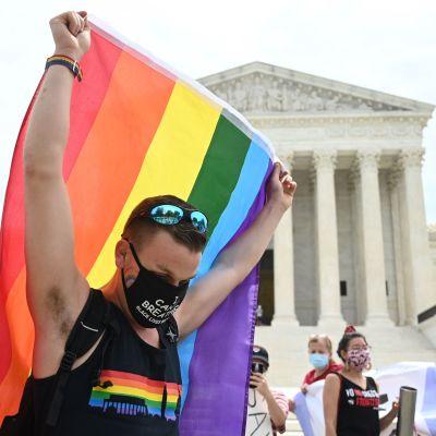 En man lyfter upp regnbågsflagga utanför USA:s högsta domstol den 15 juni 2020.