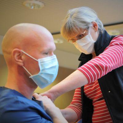 Kvinnlig sjukskötare ger spruta i axeln till en man i mörkblå sjukhusdräkt. Båda bär munskydd.