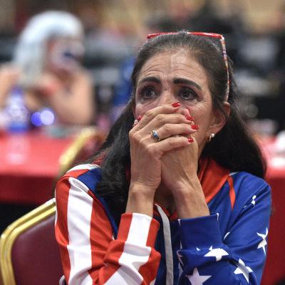 En kvinna iklädd amerikansk flaggan. Och tittar oroat på en skärm med händerna framför munnen.