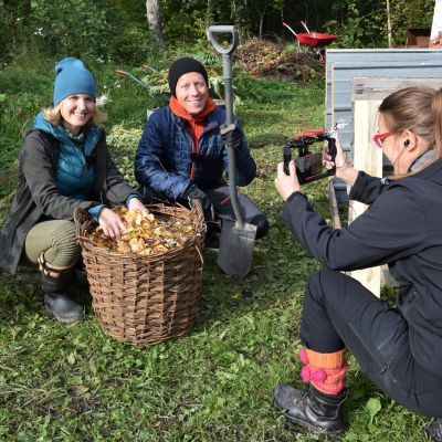 En kvinna och en man klädda i fritidskläder sitter på huk bredvid en stor korg full med löv. Framför dem sitter en kvinna på huk som filmar dem med en mobil.