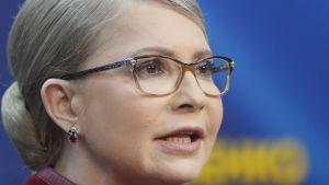 Porträttbild på Julia Tymosjenko. Hon bär glasögon och en klassisk låg hårknut i nacken. I bakgrunden syns landets blågula färger.