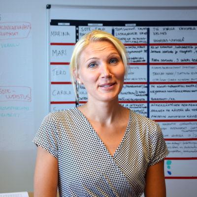 Marina Kinnunen står i sitt kontor. Hon bär en rutig klänning och i bakgrunden syns en whiteboardtavla.