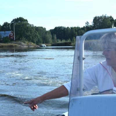 En kvinna i en båt pekar på växter i vattnet.