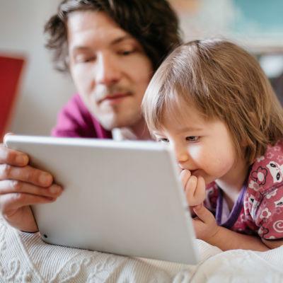 Isä ja tytär katselevat ohjelmaa mobiililaitteella.