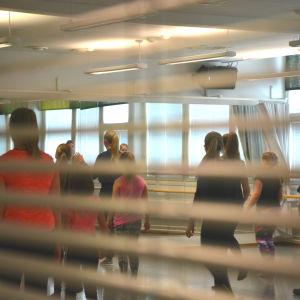 Dansare dansar i spegelsal, fotat genom fönster.