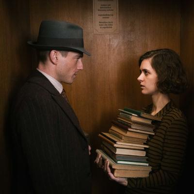 EN man i hatt och kostym står mitt emot en kvinna med en trave böcker i famnen.