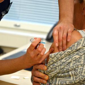 En hälsovårdare vaccinerar en kvinna genom att lägga en spruta i ena armen.