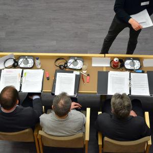 Tre män fotade uppifrån sitter på samma sida av ett bord med papperspärmar uppslagna framför sig.