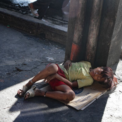 Koditon lapsi nukkuu kadulla pahvin päällä