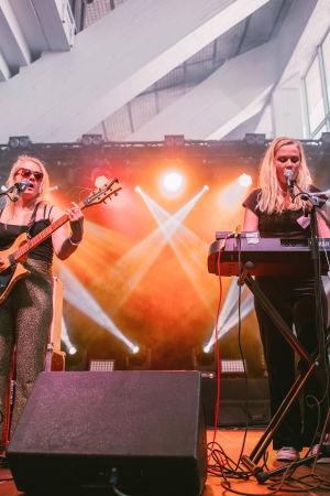 Vaaleahiuksinen nainen aurinkolasit päässään soittaa kitaraa lavalla, toinen vaaleahiuksinen nainen soittaa syntetisaattoria. Taustalla on savua ja valkeaa valoa.