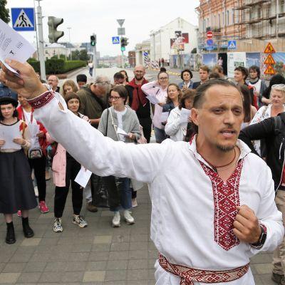 Joukko mielenosoittajia seisoo rivissä, monilla on paperilappuja käsissään. Etualalla seisoo perinnekuvioituun valkoiseen paitaan pukeutunut mies paperilappua heiluttaen.