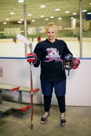 Nuori naisjääkiekkoilija jäähallissa Alaskassa.