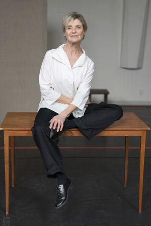 Skådespelaren Stina Ekblad poserar sittande på ett träbord, iklädd vit skjorta, svarta byxor och glansiga svarta skor. Vänster ben har hon upplyft  på bordet med vänster hand på den fotens sko.