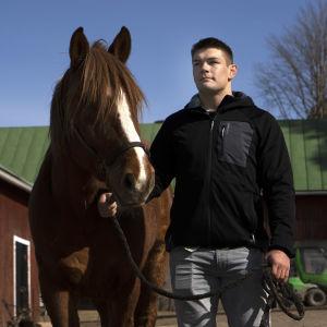 Arvi Savolainen är iklädd jacka och leder en häst.