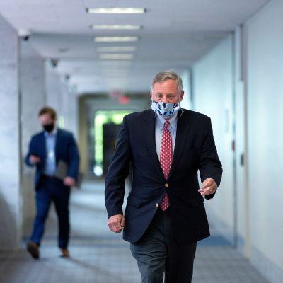 Senaattori Richard Burr kulkee senaatin käytävällä suojainmaski kasvoillaan. Hänellä on tumma puku ja punainen kravatti. Käytävä on vaalea. Kauempana taustalla kulkee toinen mies katsoen puhelintaan.