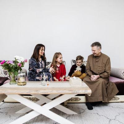 Kuvassa Nadia, Liliya, Rayan ja Mathias istuvat yhdessä sohvalla juhlavaatteissaan.
