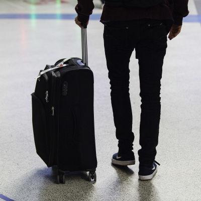 En person som har en lite kappsäck bredvid sig. Bara mänskans fötter och rygg syns.