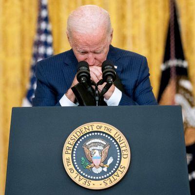 Joe Biden nojaa käsiään puhujanpönttöön ja leukaansa ristissä oleviin käsiinsä. Taustalla näkyy Yhdysvaltain lippu.