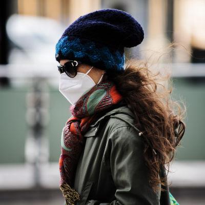 Kvinna med utekläder och rött hår samt munskydd.