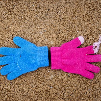 Kuvituskuvassa leikkipuissa lojuvat sininen ja pinkki sormikas.
