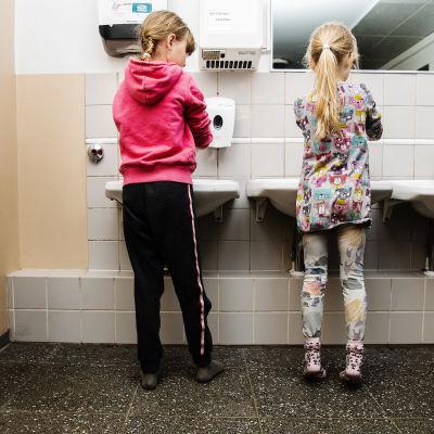 Kuvassa koululaiset pesevät käsiään.