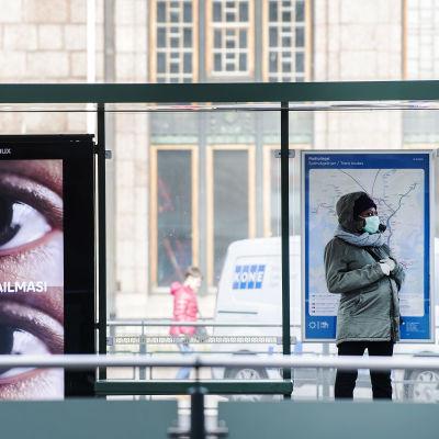 Kuvassa hengityssuojainta käyttävä nainen seisoo joukkoliikennepysäkillä.