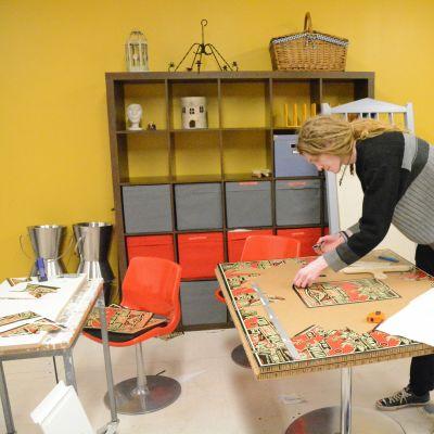 Kim Starck lutar sig över ett pysselbord.