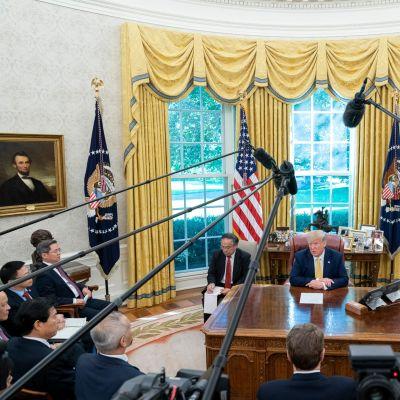 Yhdysvaltojen presidentti Donald Trump ja Kiinan varapääministeri Liu He toimittajien ympäröimänä presidentin virkahuoneessa Valkoisessa talossa.