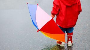 Barn i regnkläder håller i ett paraply