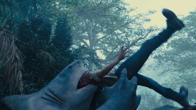 En hajmänniska i en superhjältefilm slukar en man i en djungel.