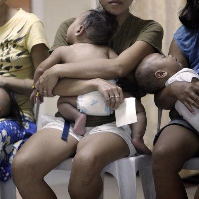 Filippinska mammor och barn köade för nödhjälp av UNFPA efter översvämningar i december 2011