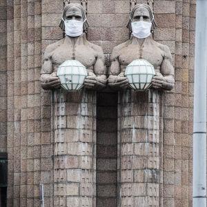 Kuvassa on maskipäiset Lyhdynkantaja-patsaat ja näkymä Helsingin rautatieasemalle elokuussa 2020.