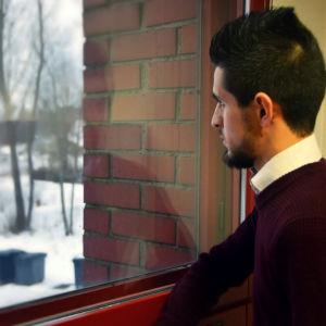 Saad Almosly tittar ut genom ett fönster.
