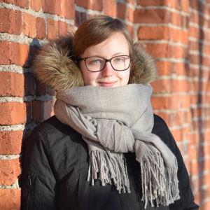 Porträtt på Maria Hagberg, står framför rödtegelvägg i solsken, grå halsduk runt halsen.