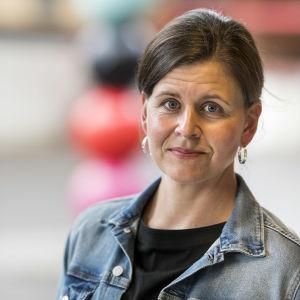 en kvinna i brunt uppsatt hår och jeansjacka