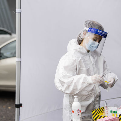 En sjukskötare behandlar ett nytaget coronavirustest vid en drive in testningsplats.