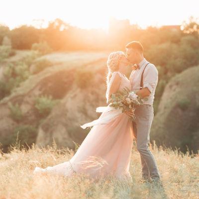 Man och kvinna klädd i böljande klänning kysser varandra på sommaräng
