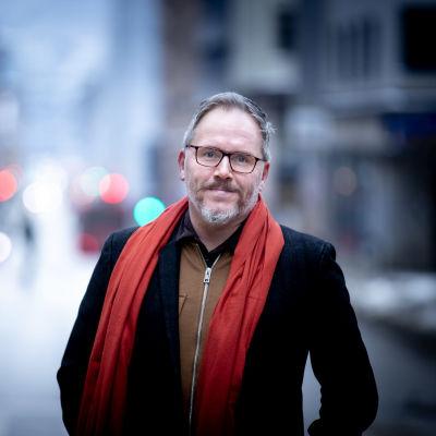 Porträttfoto taget utomhus av man i medelålder, grått hår, glasögon, grått skägg, svart kappa och röd halsduk.