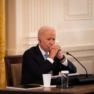 Joe Biden sitter vid ett bord med händerna framför ansiktet och en orolig min.
