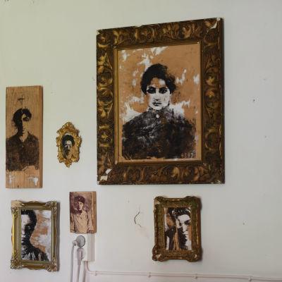 Tavlor, porträtt i bruna nyanser på en vit vägg