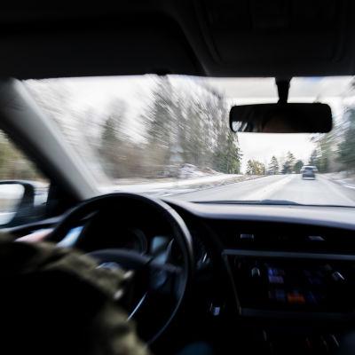 Bild inifrån personbil, man ser ratt och instrumentpanel och landsvägen. Bilen är i trafik.