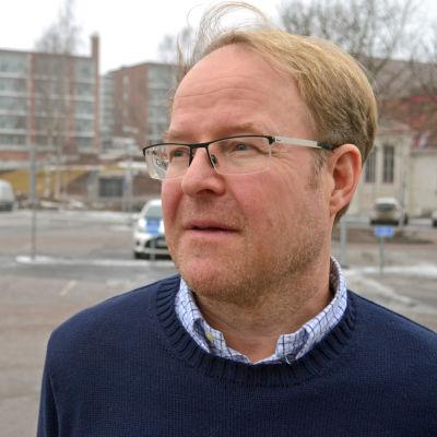Taneli Antikainen poserar på en parkeringsplats, tittar mot vänster.