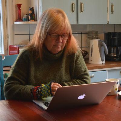Jaana Kapari-Jatta sitter vid köksbordet, framför sin dator och skriver.