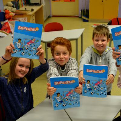 Fyra barn tittar uppåt mot kameran och håller upp sina matematikböcker i luften.