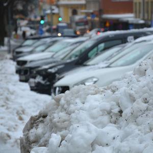 Flera bilar står parkerade i rad framför en stor snöhög.